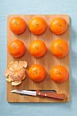 Ganze Mandarinen und eine geschälte Mandarine auf Holzbrett