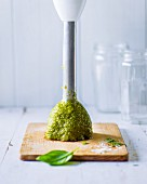 Green pesto on a hand blender