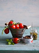 An arrangement of tomatoes, a tin of tuna fish, a jar of capers and basil