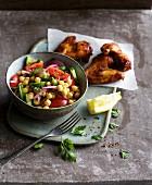 Würziger Kichererbsensalat mit buntem Gemüse als Beilage zu Hähnchen