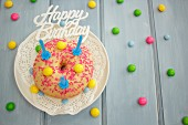 A doughnut with colourful chocolate beans for a birthday