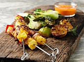 Grilled chicken skewers with lemons and vegetables on a wooden board