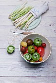 White and green asparagus on a wooden board, asparagus peelings, a peeler and a bowl of various tomatoes