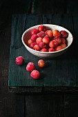 A bowl of frozen cherries on an old wooden table