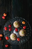 Shortcrust tartlets with pistachios and cherries on a vintage cake stand