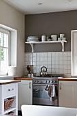 Wohnliche, helle Küche mit grauer Fläche über weissen Wandfliesen