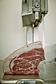 Schweinefleisch in einer Metzgerei mit Schneidemaschine in Scheiben schneiden