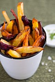 Winter vegetable chips in a cup next to a herb quark dip
