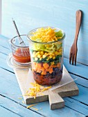 A layered sweet potato salad with beans in a glass