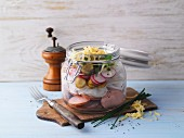 A layered sausage salad with radishes in a jar