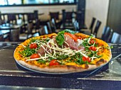 A pizza with Parma ham, rocket and cherry tomatoes on a restaurant bar
