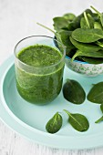 A spinach smoothie in a glass with fresh spinach
