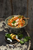 Coconut and carrot salad with chicken skewers