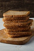 Slices of wholemeal bread stacked on a wooden board