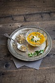 Curried carrot soup with feta cheese, spicy mixed nuts and parsley