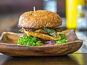 A burger on a wooden dish on a restaurant table