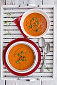 Two bowls of cream of tomato soup with fresh basil on a wooden tray