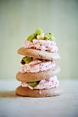 A stack of meringue biscuits with strawberry cream and kiwis