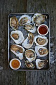 Raw oysters in half shells with condiments