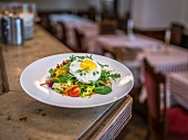 A mixed salad with a fried egg on a restaurant counter