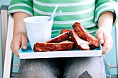 A child holding a tray of ribs and a drink