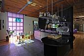 Essplatz mit transparenten Kunststoffstühlen und lilafarbener Jalousie in offener Küche einer Loftwohnung mit Industriecharme
