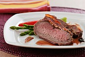 Beef fillet wrapped in ham served with green asparagus