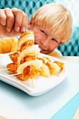 A blonde boy with fruity turkey skewers