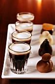 Pralinen und schwarzer Kaffee mit Milchschaum