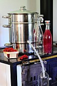 A juicer, fresh berries and bottle of juice on an old kitchen stove