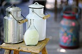 Milk churns and a bottle of milk on a wooden stool