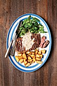 Grilled rib-eye steak with fried potatoes, lettuce and pepper sauce