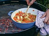 Tomaten-Artischocken-Sauce über der Grillglut erwärmen