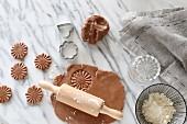 Glutenfreie Teigrohlinge, ausgerollter Mürbteig mit Nudelholz, Ausstechförmchen und eine Schale mit glutenfreiem Mehl auf Marmorplatte