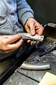 Messer-Herstellung, Griff aus Horn wird zurecht gesägt