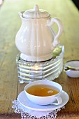 A cup of tea and a teapot on a teapot warmer