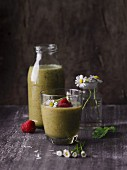 A raspberry and banana smoothies with leaves and daisies