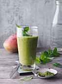 A green matcha and peppermint smoothie with dates, figs and mango