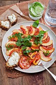 Nectarine and tomato carpaccio with goat's cream cheese on bread