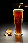 A glass of dark beer and crisps