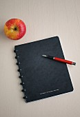A notebook with a pencil and an apple