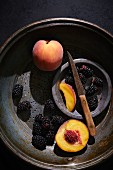 Fresh peaches and blackberries with a knife in a vintage colander