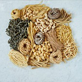 Various types of pasta on a white surface (seen from above)