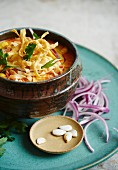Khao Soi soup garnished with red onions, limes, pumpkin seeds and coriander