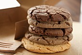 A stack of assorted chocolate chip cookies next to a box