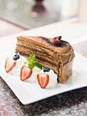 A slice of tiramisu chocolate cake served with whipped cream and berries
