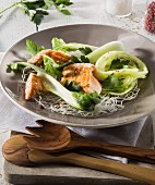 Salmon and bok choy on a bed of glass noodles on a plate with wooden cutlery