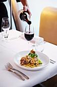 Kellner schenkt Rotwein zu knusprig gebratener Ente mit Chinakohl