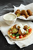 Falafel on pita bread with a vegetable salad and tahini