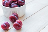 Plums in a bowl and on a wooden surface